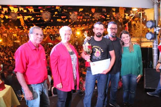 Marcador de quadrilha recebe premiação ladeado pelos jurados